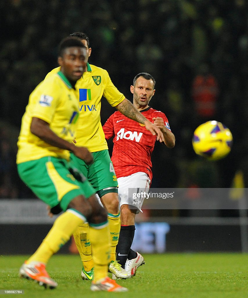 """Manchester United's Welsh midfielder Ryan Giggs (R) watches the ball during the English Premier League football match between Norwich City and Manchester United at Carrow Road stadium in Norwich, England on November 17, 2012. Norwich City won the game 1-0. USE. No use with unauthorized audio, video, data, fixture lists, club/league logos or """"live"""" services. Online in-match use limited to 45 images, no video emulation. No use in betting, games or single club/league/player publications."""