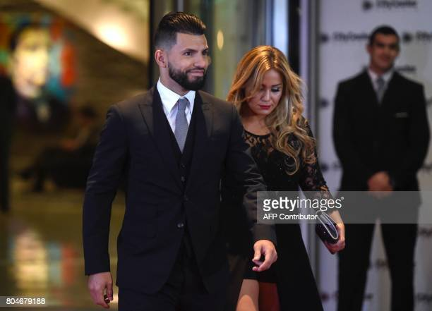 Manchester's City footballer Argentine Sergio Aguero and his girlfriend walk on a red carpet upon arrival to attend Argentine football star Lionel...