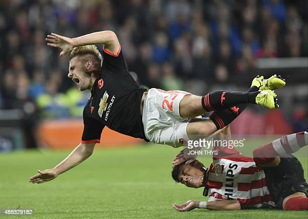 Manchester's defender Luke Shaw is challenged by Eindhoven's Mexican defender Hector Moreno during the UEFA Champions League Group B football match...