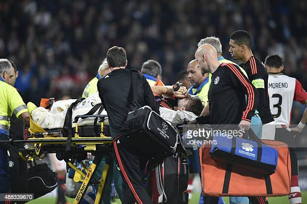 Manchester's Luke Shaw leaves the field after being injured during the UEFA Champions League Group B football match between PSV Eindhoven and...