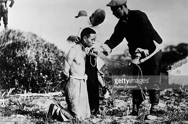 Manchurian henchmen in the service of Japan put a noose around the neck of a Chinese patriot who has refused to accept the Japanese invasion and...