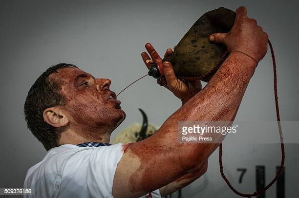 A mancovered in cow blood and wearing a Momotxorro costume drinks from a pouch before a parade during the annual Momotxorro carnival in Alsasua...