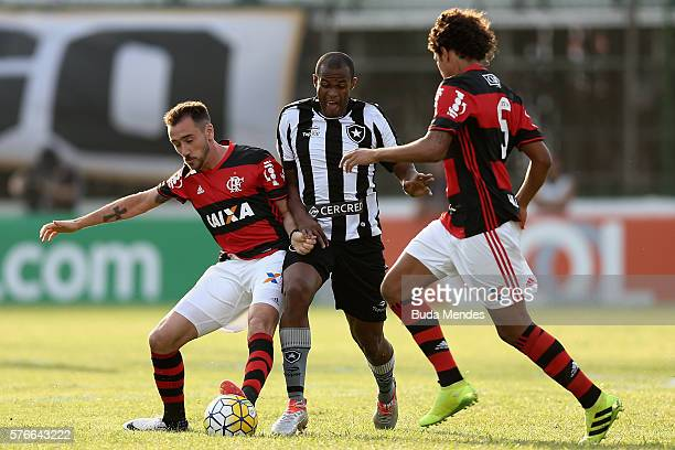 Mancuello and Willian Arao of Flamengo struggle for the ball with Airton of Botafogo during a match between Flamengo and Botafogo as part of...