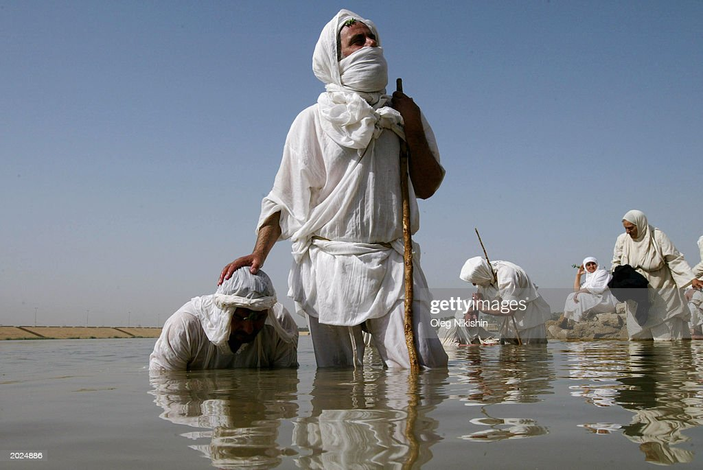 Mandaean Sabian cleric baptizes a man on the banks of the Tigris River as they participate in a ceremony known as the Golden Baptism which is one of...