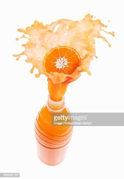 Mandarin orange juice splashing out of bottle on orange