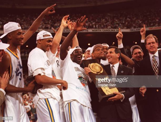 MEN''S BASKETBALL TEAM CELEBRATES WITH THE CHAMPIONSHIP TROPHY AFTER DEFEATING ARKANSAS 8978 IN THE FINALS AT THE KINGDOME IN SEATTLE WASHINGTON...