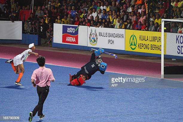 Mandeep Singh of India hits past Malaysia's goalkeeper Subramiam Kumar to score the second goal of the match at the Sultan Azlan Shah Cup men's field...