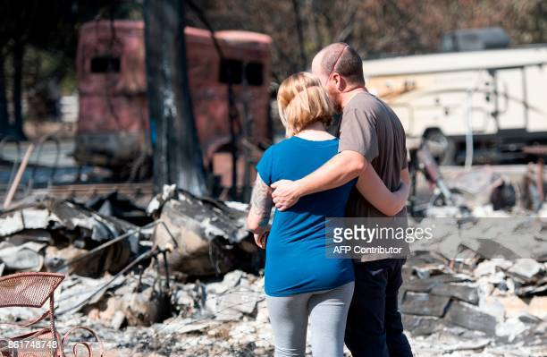 Mandi and Lane Summit embrace before their firedestroyed home in Redwood Valley California on October 15 2017 The death toll from California's...