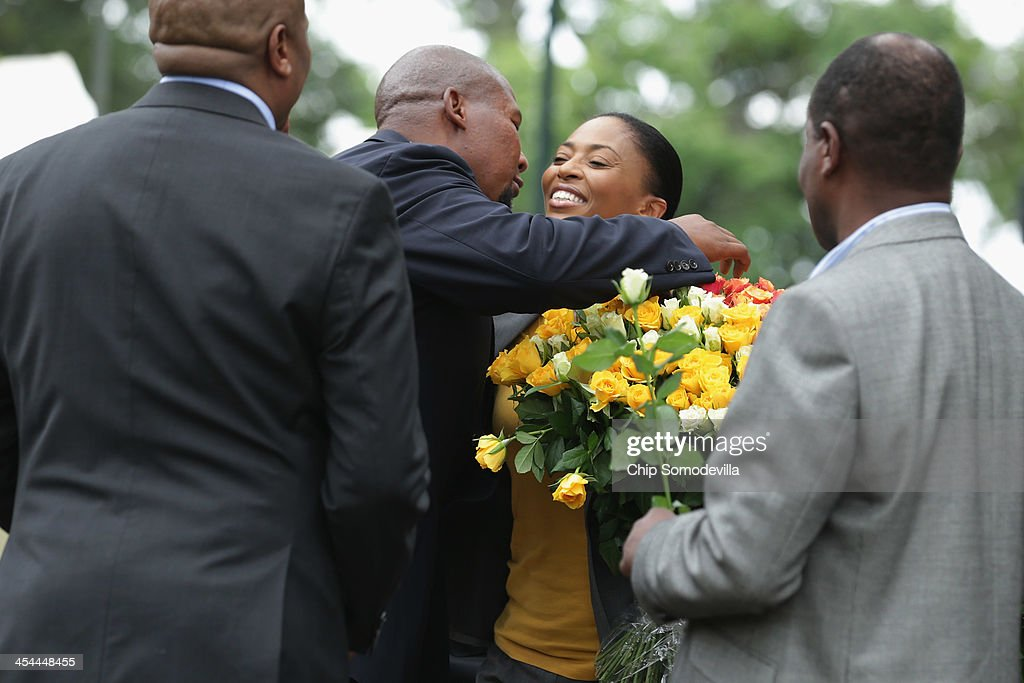 <a gi-track='captionPersonalityLinkClicked' href=/galleries/search?phrase=Mandla+Mandela&family=editorial&specificpeople=5849591 ng-click='$event.stopPropagation()'>Mandla Mandela</a> (2L) embraces Jessica Motaung, daughter of Kaizer Chiefs football club chairman Kaizer Motaung, as she, her family and members of the team arrive at the home of former South African President Nelson Mandela to pay their respects to Mandela's family in the Houghton Estates neighborhood December 9, 2013 in Johannesburg, South Africa. Mandela, also known as Madiba, passed away on the evening of December 5, 2013 at his home in Houghton at the age of 95. Mandela became South Africa's first black president in 1994 after spending 27 years in jail for his activism against apartheid in a racially-divided South Africa.