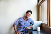 Portrait of a handsome modern man smiling with laptop at cafe