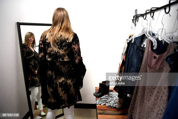 Mandy Anderson looks in the mirror after trying on a piece as she goes shopping at Peak Thrift store on May 23 2017 Mandy picks out a few items to...