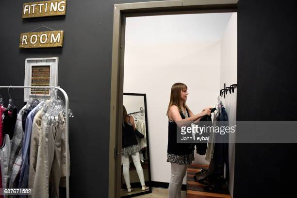Mandy Anderson sorts through some clothes she picked out to try on as she goes shopping at Peak Thrift store on May 23 2017 Mandy picks out a few...
