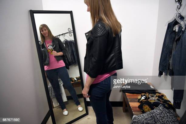 Mandy Anderson tries on a Looney Tunes shirt with a jacket as she goes shopping at Peak Thrift store on May 23 2017 Mandy picks out a few items to...