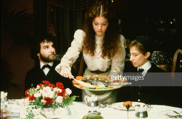 Mandy Patinkin looks lovingly at Amy Irving as she serves Barbra Streisand stands on a ferry boat in a scene in the movie 'Yentl' circa 1983
