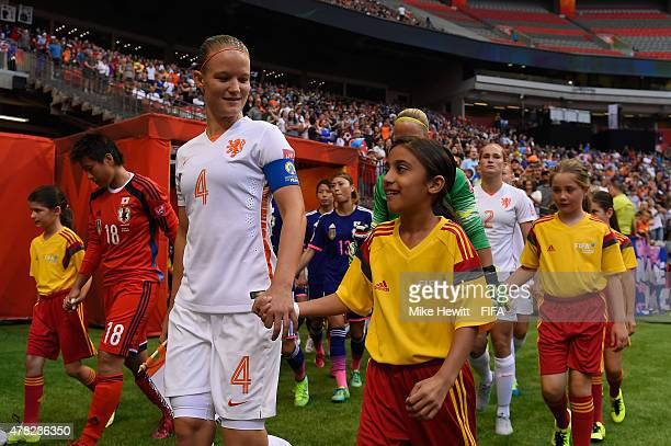 Mandy van den Berg of Netherlands walks out with a mascot for the FIFA Women's World Cup 2015 Round of 16 match between Japan and Netherlands at the...