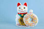 a maneki neko presenting a multicolor donuts on a doily paper and a pop colorful background.Minimal quirky color still life photography