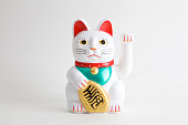a Maneki-neko plastic cat, Symbolizing luck and wealth, on a white background