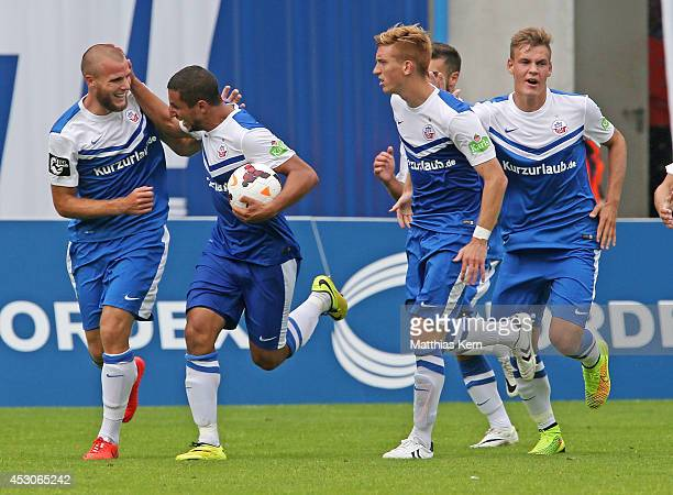 Manfred Starke of Rostock jubilates with team mates after scoring the second goal during the third league match between FC Hansa Rostock and Rot...