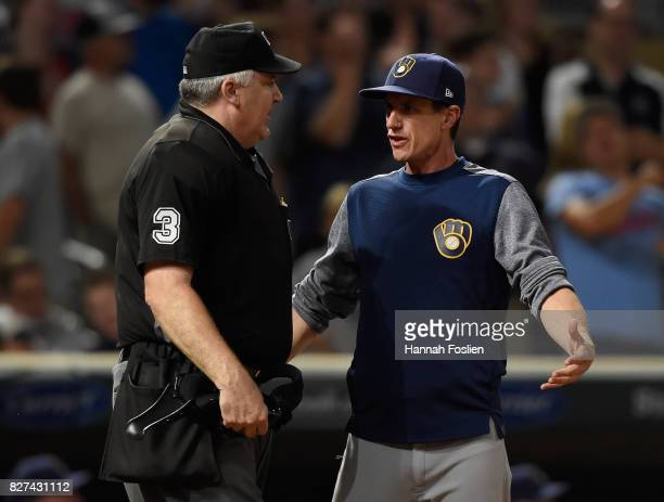 Manger Craig Counsell of the Milwaukee Brewers speaks with home plate umpire Bill Welke after a balk scored a run for the Minnesota Twins during the...