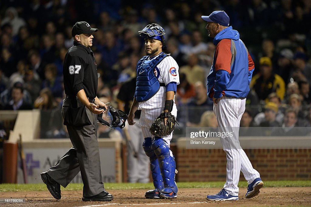 Manger Dale Sveum #4 of the Chicago Cubs (R) argues a call with home plate umpire Scott Barry #87 as catcher Dioner Navarro #30 of the Chicago Cubs stands on the field during the third inning against the Pittsburgh Pirates at Wrigley Field on September 24, 2013 in Chicago, Illinois.