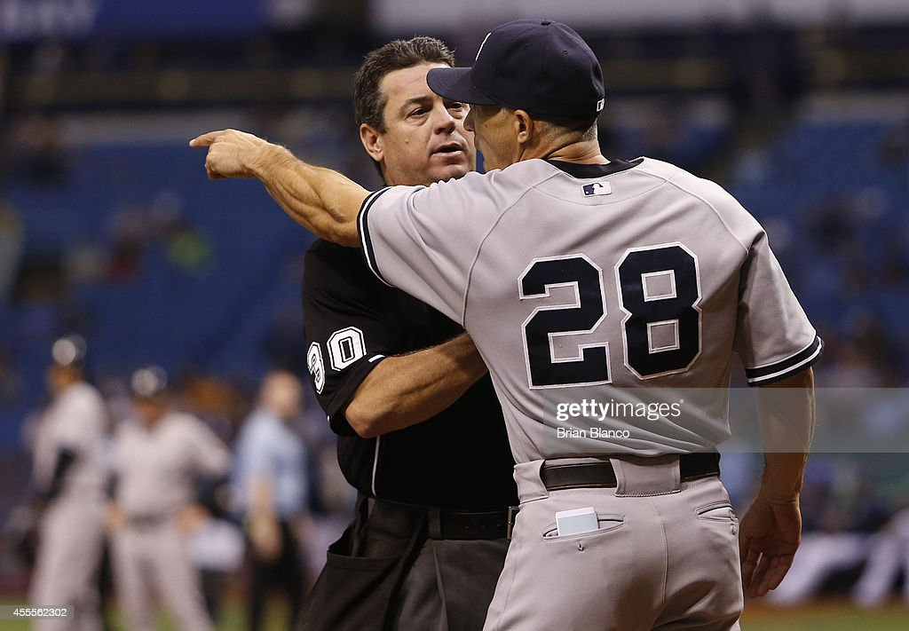 Manger Joe Girardi of the New York Yankees is held back by home plate umpire Rob Drake as he points back toward the pitcher's mound after pitcher...