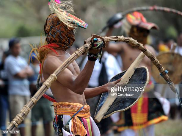A Manggarai man performs during a Caci a ritual whipping fight in Nusa Dua on the Indonesian resort island of Bali on August 20 2017 Caci is a key...
