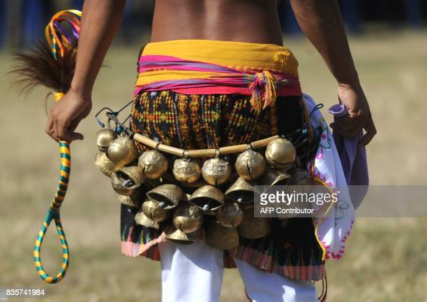 A Manggarai man wearing bells performs during a Caci a ritual whipping fight in Nusa Dua on the Indonesian resort island of Bali on August 20 2017...