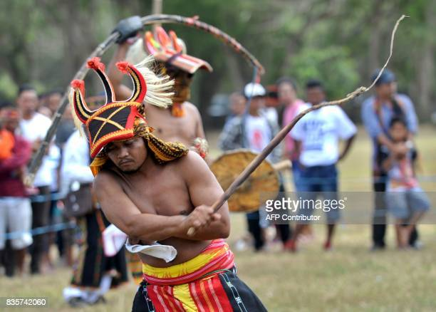 Manggarai men perform during a Caci a ritual whipping fight in Nusa Dua on the Indonesian resort island of Bali on August 20 2017 Caci is a key...