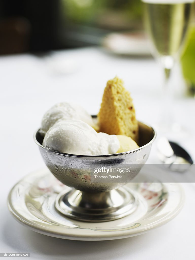 Mango and lemon gelato with cookie, glass of champagne in background : Stock Photo