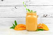 Tropical mango coconut smoothie in a mason jar glass, on a rustic white wood background