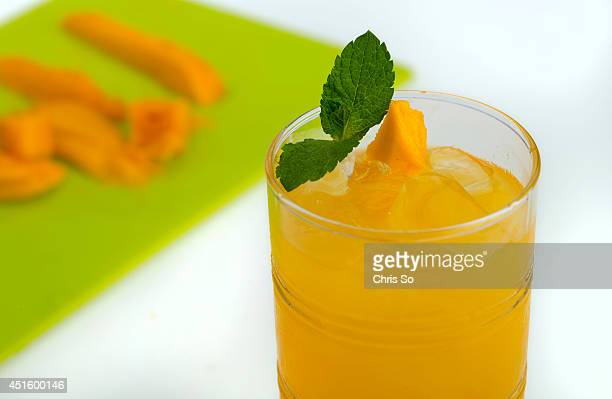 Mango Green Tea Splash is a nonalcoholic cocktail with a mango chunk and fresh mint garnish for Summer drinks and cocktails and book series June 30...