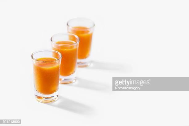 Mango juice displayed in shot glasses