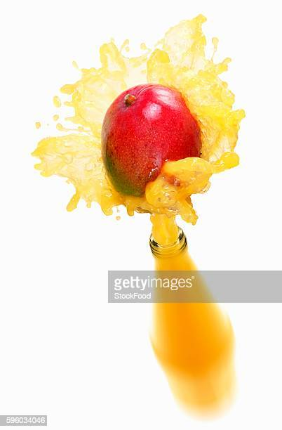 Mango juice splashing out of bottle