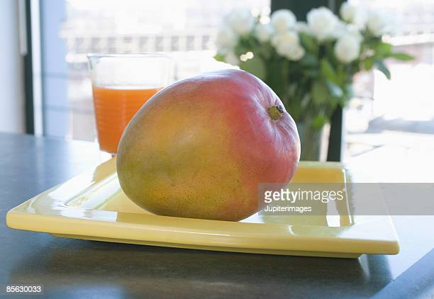 Mango on plate with flowers and glass of juice