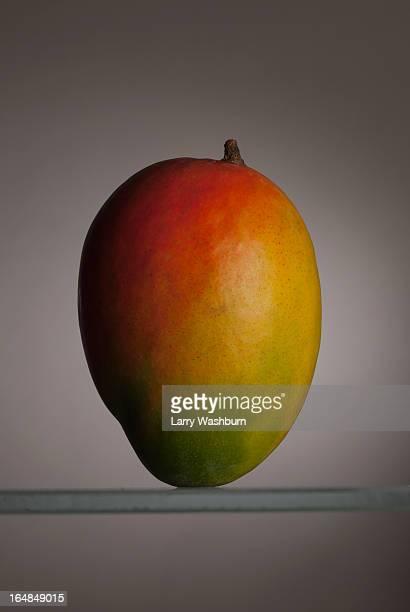 A mango standing up on a glass shelf