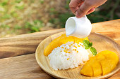 Mango with sticky rice. Woman hand pouring coconut milk on top with beans topping. Favorite thai dessert in summer season. Sweet and freshness tast.