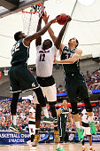 Mangok Mathiang of the Louisville Cardinals shoots the ball against Branden Dawson and Gavin Schilling of the Michigan State Spartans during the East...