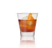Manhattan drink in a rocks glass single ice cube and orange peel garnish on a white background