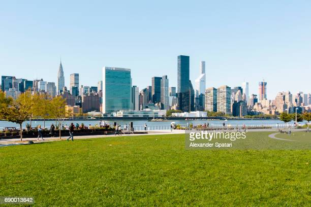 Manhattan skyline along East River with green lawn on the foreground, New York City, USA