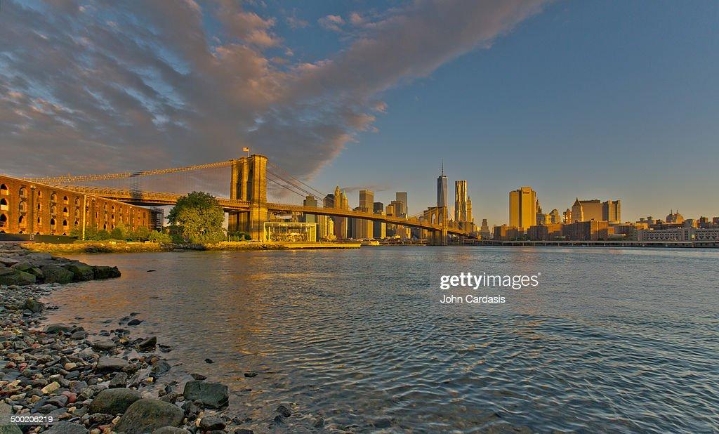 Manhattan skyline and Brooklyn Bridge at sunrise
