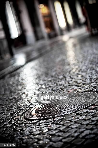 Bouche d'égout couverture sur la rue pavée wet setts en granit