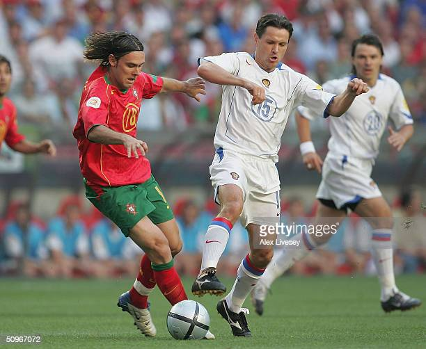 Maniche of Portugal clashes with Dmitry Alenichev of Russia during the UEFA Euro 2004 Group A match between Russia and Portugal at the Luz Stadium on...