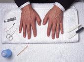 Manicure equipment around man's hands on towel, overhead view