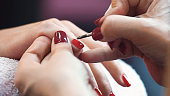 Closeup side view unrecognizable woman having her fingernails painted in red by a professional nail artist. Her hand is placed on a towel. Shot over blue purple background.