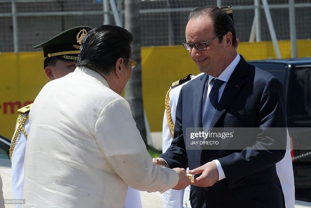 Manila Mayor <a gi-track='captionPersonalityLinkClicked' href=/galleries/search?phrase=Joseph+Estrada&family=editorial&specificpeople=553277 ng-click='$event.stopPropagation()'>Joseph Estrada</a> (L) presents a symbolic Key of the City to French President Francois Hollande (R) after a wreath laying ceremony at the monument to national hero Jose Rizal in Manila on February 26, 2015. Hollande is on a two-day visit to the Philippines, aimed at building momentum for climate talks in Paris.