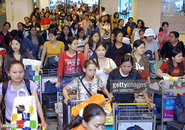 A group of Filipino domestic workers exit the airport after collecting their baggage from the carousel at Manila's airport 15 August 2006 after...