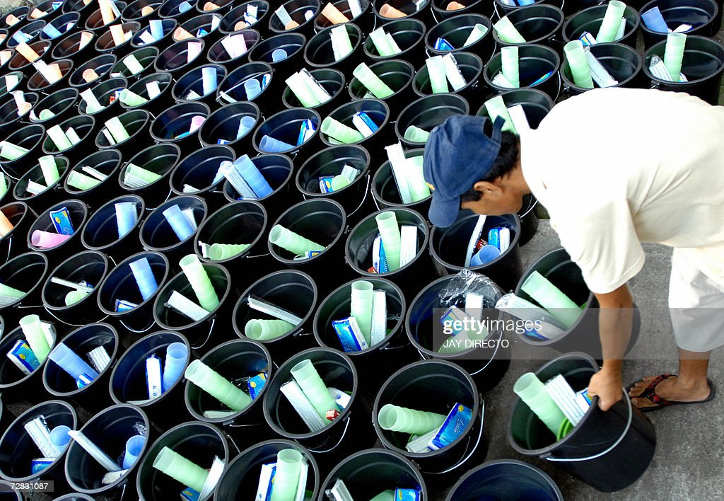 A Worker at the Catholic Bishops Conference of the Philippines (CBCP) arranges buckets containing bathroom and kitchen accessories in Manila, 15 December 2006, prior to their distribution amongst surviving victims of the mudflow triggered by Typhoon Durian. The strongest typhoon to hit the Philippines in living memory unleashed avalanches of volcanic debris which buried more than 700 villages and farms, leaving more than 2,000 people dead or missing, according to the civil defense office. AFP PHOTO/Jay DIRECTO