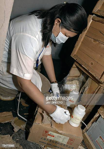 An unidentified chemist of the Philippine National Bureau of Investigation checks chemicals seized in Manila 16 February 2007 after the raid of a...