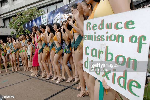 Contestants vying for the Miss PhilippinesEarth 2007 in their swimsuits pose for press photographers carrying plants and environmental slogans in...