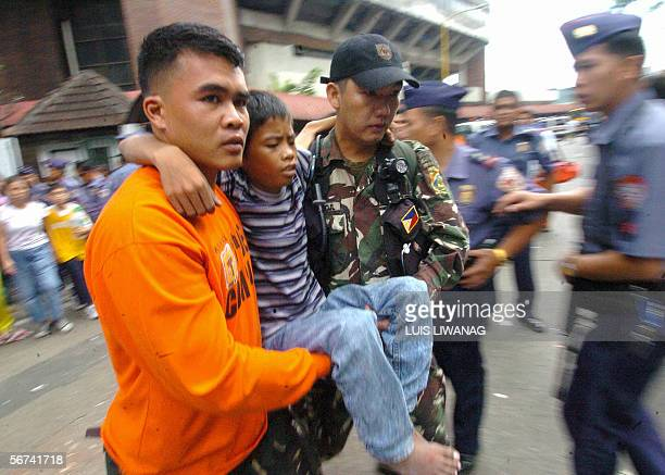 Rescuers carry a child who was hurt during the stampede infront of a stadium in Manila 04 February 2006 Eightyeight people were killed and as many as...